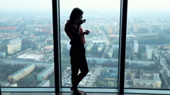 Silhouette of young, pensive woman drinking coffee and admire view from window, Stock Footage
