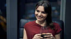 Stock Video Footage of Pretty woman relaxing  and drinking wine while sitting on armchair  during night