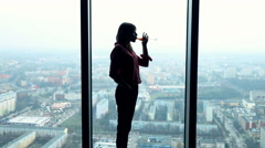 Silhouette of young woman drinking wine  and admire view from window, 240fps Stock Footage