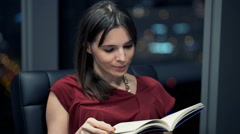 Young, pretty woman reading book on armchair during night Stock Footage