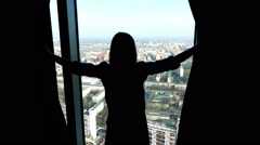 Silhouette of young woman unveil curtain and looking from the window, 240fps - stock footage
