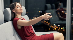 Young woman watching TV and drinking wine on sofa at night Stock Footage