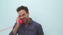 Cute stylish guy talking on the pink telephone Stock Footage