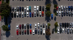 Aerial, vertical - Tracking shot of a car leaving shopping center parking lot - stock footage