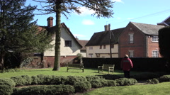 Lavenham England village park woman on bench 4K Stock Footage