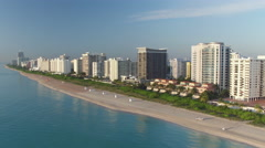 AERIAL: Flying along sunny Miami Beach with tall skyscrapers buildings - stock footage