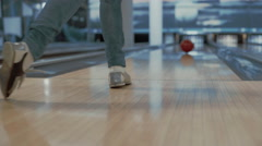 Young woman is throwing ball in a bowling club, enjoys successful throw - stock footage