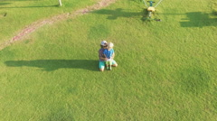 Young father with adorable son controlling drone on green lawn together. Stock Footage