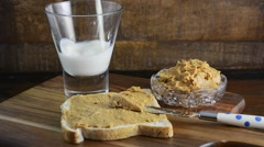 Pouring glass of milk with peanut butter on whole grain bread on rustic wood  Stock Footage