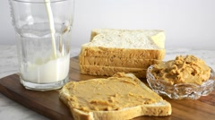Peanut butter on bread with milk, pouring milk into glass. Stock Footage