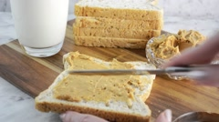 Peanut Butter with Glass of Milk, spreading peanut butter on to bread. Stock Footage
