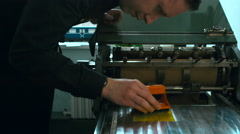 Caucasian male preparing stamp for a letterpress print. Dolly out Stock Footage