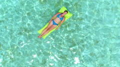 AERIAL: Woman lying on inflatable air mattress in vast ocean - stock footage