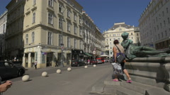 People walking, riding bikes and sitting on stairs in Neuer Markt in Vienna Stock Footage