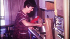Housewife cooks over the kitchen stove at home - 985 vintage film home movie Stock Footage