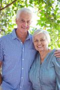 Cheerful senior couple with arm around - stock photo