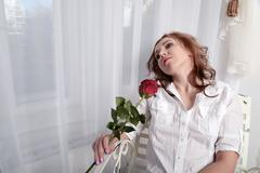 woman with a rose sitting on a chair near the window - stock photo