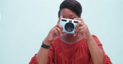 Childish young african woman taking a photo with vintage camera - stock footage