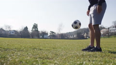 Footballer practising kick ups in the park on a bright morning Stock Footage