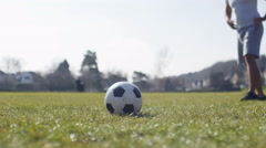 4K Unseen man kicking a football in a park, in slow motion Stock Footage