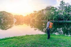 Man hiker standing near beautiful lake at sunset. - stock photo