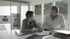 Mature adult male teaching teenage child in kitchen - stock footage