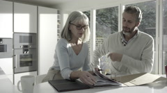 Adult male with senior female looking at personal finance in kitchen Stock Footage
