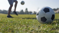 Footballer doing kicks ups as a soccer ball is in the foreground, in slow motion - stock footage