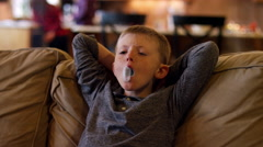 Boy relaxing on the couch and chewing bubble gum, slow motion Stock Footage