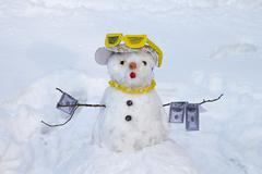 snowman in cap and sunglass hold 100 dollars note - stock photo