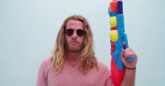 Serious hipster goofing around with water gun Stock Footage