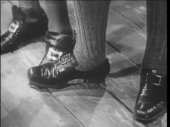 Stock Video Footage of Man dressed in pilgrim shoes stepping on someone's foot, 1940s
