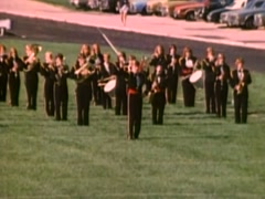 Drum major leading marching band across football field, 1980s Stock Footage