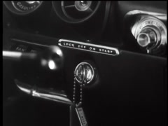 Closeup of woman turning ignition key in car, 1960s Stock Footage