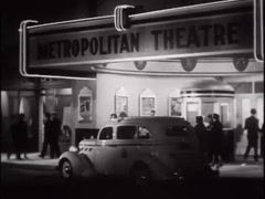 Cars driving past theater at night, 1930s Stock Footage