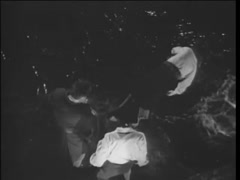 Two men pushing man off cliff into water at night, 1940s Stock Footage