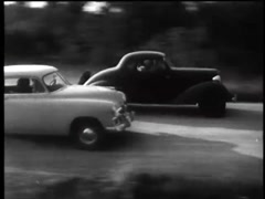 Vintage cars racing and kicking up dust on country road, 1960s Stock Footage