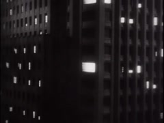 Pan up to top of skyscraper at night, 1930s Stock Footage