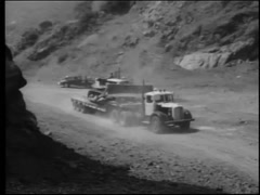 Truck carrying bulldozer following motorcycle police on dirt road, 1950s Stock Footage