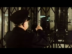 Security guard locking gates in front of office building, 1960s Stock Footage
