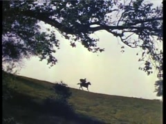 Wide shot of  man in cape horseback riding across hill, 1940s - stock footage