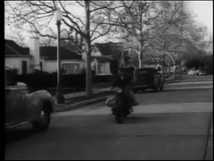 Paperboy on motor scooter delivering newspapers,1950s Stock Footage