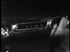 Closeup of woman quickly turning knob on car radio, 1960s - stock footage
