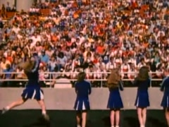 Stock Video Footage of Cheerleaders facing clapping spectators at high school football game, 1980s
