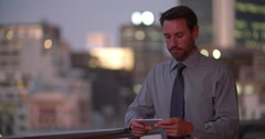 Businessman hodling smartphone in horizontal position on office balcony Stock Footage