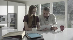 Mature adult male teaching teenage daughter in kitchen - stock footage