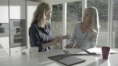 Adult woman with senior mother looking at personal finance in kitchen - stock footage