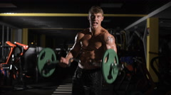 Overcoming Young adult bodybuilder doing weight lifting in gym - stock footage