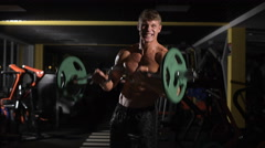 On the verge of possibilities. Young adult bodybuilder doing weight lifting in - stock footage