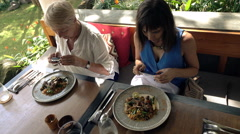 Mother and daughter take photos of their food in bar Stock Footage